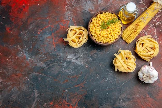 Powyżej widok niegotowanych trzech porcji makaronów spaghetti i motylkowych w brązowej misce i butelce z olejem czosnkowym i zieloną cebulą na stole o mieszanych kolorach