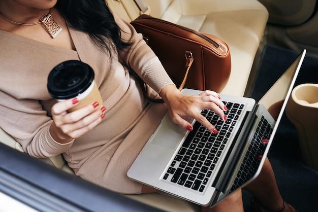 Powyżej widok nierozpoznawalnej bizneswoman z jednorazową filiżanką kawy piszącą na laptopie w taksówce