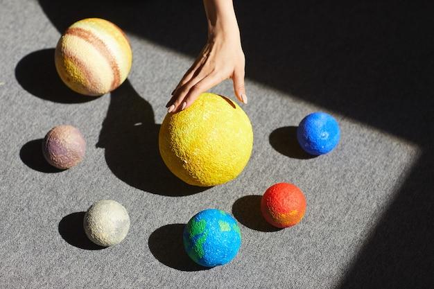 Powyżej widok nierozpoznawalnej kobiety umieszczającej w świetle na podłodze modele planet według układu słonecznego