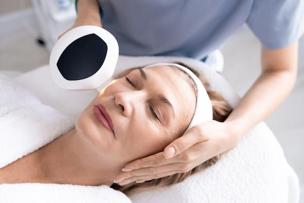 Powyżej widok nierozpoznawalnej kosmetyczki wykorzystującej urządzenie laserowe podczas wykonywania zabiegu odmładzania skóry dojrzałej kobiety