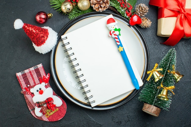 Powyżej widok notatnika z długopisem na talerzu obiadowym choinka gałęzie jodły szyszka pudełko pudełko czapka świętego mikołaja skarpety świąteczne na czarnym tle