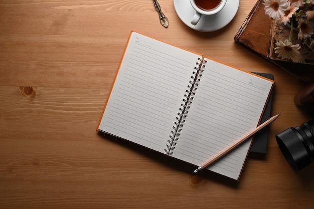 Powyżej widok obszaru roboczego freelancera z aparatem, notatnikiem, filiżanką kawy i ołówkiem na drewnianym tle.