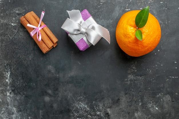 Powyżej widok organicznej świeżej pomarańczy z łodygą i liściem w pobliżu prezentu i limonek cynamonowych na ciemnym tle