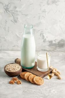 Powyżej widok otwartej szklanej butelki wypełnionej łyżką mleka i płatkami owsianymi w brązowych garnkach na lodowym tle