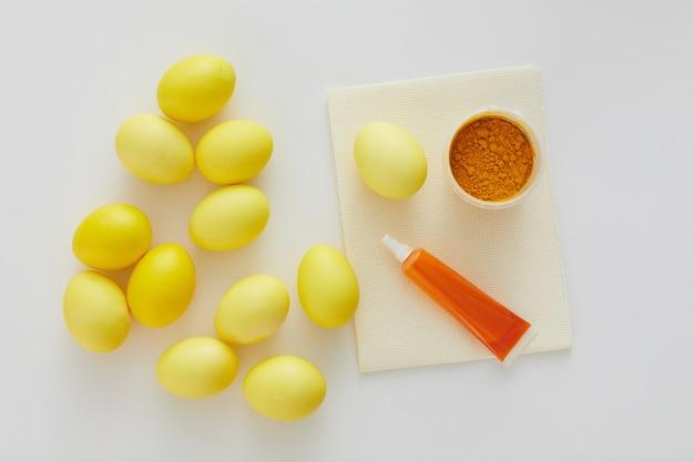 Powyżej widok pastelowych żółtych pisanek z naturalnym barwnikiem ułożonym w minimalnej kompozycji na białym tle, miejsce na kopię
