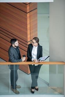 Powyżej widok pewnych siebie ekspertów biznesowych w dziedzinie odzieży wizytowej, rozmawiających na korytarzu o finansach i budżecie