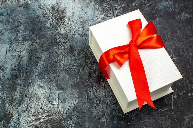 Powyżej widok pięknie zapakowanych pudełek na prezenty przewiązanych czerwoną wstążką po prawej stronie na ciemnym