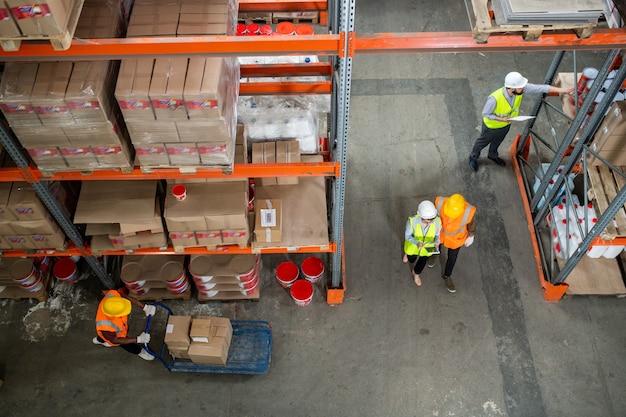 Powyżej widok pracowników magazynu w kaskach i kamizelkach odblaskowych pracujących z pudłami i sortujących je na półkach