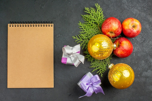 Powyżej widok prezentów i naturalnych organicznych akcesoriów do dekoracji świeżych jabłek i zeszytów na czarnym stole