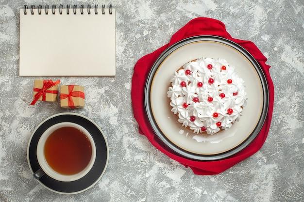 Powyżej widok pysznego kremowego ciasta ozdobionego owocami na czerwonym materiale