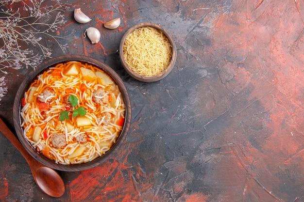 Powyżej widok pysznej zupy z makaronem z kurczakiem i niegotowanym makaronem w małej brązowej misce i łyżką czosnku na ciemnym tle