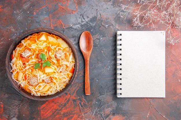 Powyżej widok pysznej zupy z makaronem z kurczakiem w brązowej misce i łyżką obok notatnika na ciemnym tle