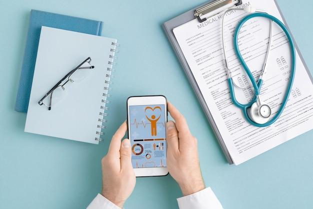 Powyżej widok rąk kardiologa ze smartfonem przewijających online statystyki medyczne wśród dokumentów w schowku i zeszytów