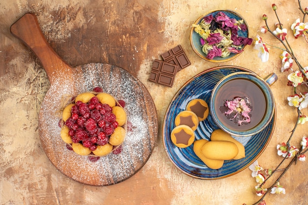 Powyżej widok różnych ciastek i miękkiego ciasta filiżanka herbaty i kwiaty batony czekoladowe