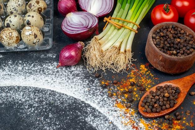 Powyżej widok różnych świeżych produktów spożywczych i wolnej przestrzeni z mąką wokół ciemnego stołu