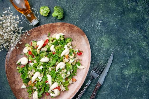 Powyżej widok sałatka ze świeżych warzyw wewnątrz eleganckiego talerza ze sztućcami na ciemnoniebieskim tle