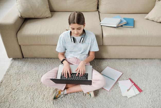 Powyżej widok skoncentrowanej nastolatki siedzącej na dywanie i używającej laptopa podczas nauki