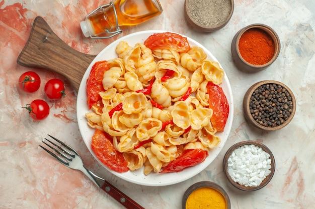 Powyżej widok smaczne conchiglie na białym talerzu na drewnianej desce do krojenia