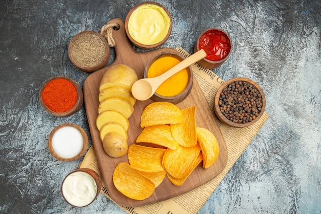 Powyżej widok smacznych domowych frytek pokroić plastry ziemniaków na drewnianej desce do krojenia i różne przyprawy w gazecie na szarym stole