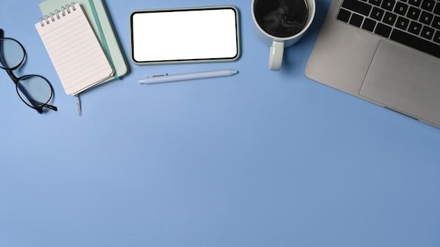 Powyżej widok smartfona, laptopa, notebooka i filiżanki kawy na niebieskim tle.