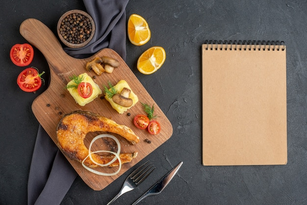 Powyżej widok smażonej mączki rybnej z pieczarkami warzywa ser na drewnianej desce plasterki cytryny pieprz na ciemnym kolorze zestaw ręczników sztućce i notatnik na czarnej trudnej powierzchni