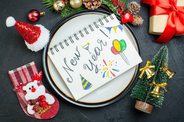 Powyżej widok spiralnego notatnika z długopisem na talerzu obiadowym choinka gałęzie jodły pudełko z szyszkami szyszka święty mikołaj skarpeta świąteczna na czarnym tle