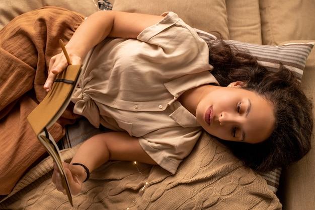 Powyżej widok spokojnej, rozmarzonej kobiety rasy mieszanej leżącej na łóżku i czytającej książkę