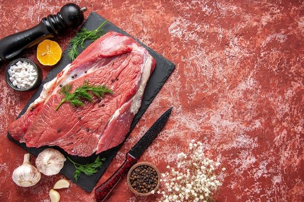 Powyżej widok surowego świeżego czerwonego mięsa z zielenią i pieprzem na czarnej desce nóż czosnek cytryna przyprawy drewniany młotek cytryna po prawej stronie na pastelowym czerwonym tle olejnym