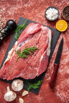 Powyżej widok surowego świeżego czerwonego mięsa z zielonym i pieprzem na czarnej desce nóż czosnek cytryna przyprawy drewniany młotek cytryna na pastelowym czerwonym tle olejowym