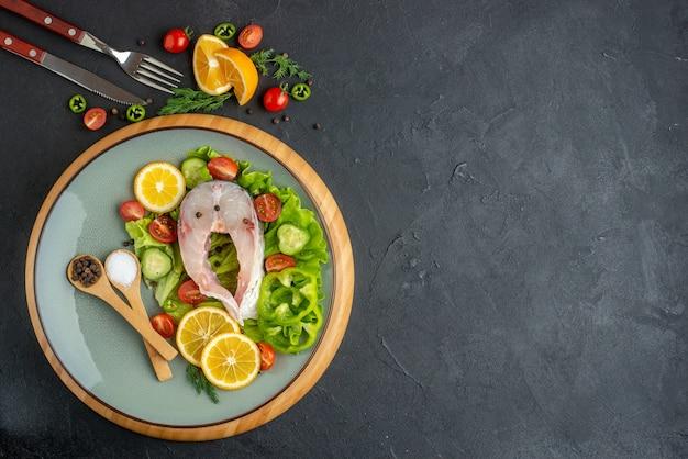 Powyżej widok surowej ryby i świeżych pokrojonych warzyw plasterki cytryny przyprawy na szarym talerzu i sztućce ustawione po prawej stronie na czarnej postrzępionej powierzchni