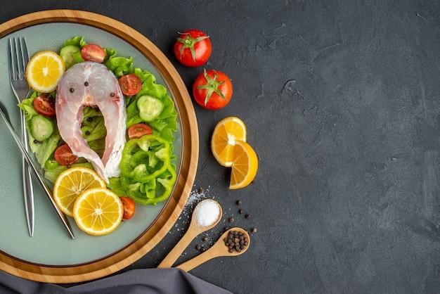 Powyżej widok surowej ryby i świeżych warzyw plasterki cytryny i sztućce ustawione na szarym talerzu przyprawy ciemny ręcznik po lewej stronie na czarnej powierzchni