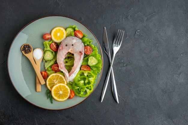 Powyżej widok surowej ryby i świeżych warzyw, plasterki cytryny, przyprawy na szarym talerzu i sztućce ustawione na czarnej powierzchni