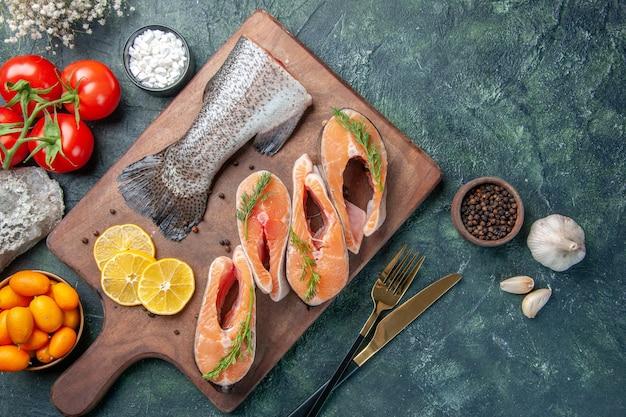 Powyżej widok surowych ryb plasterki cytryny papryka zielona na drewnianej desce do krojenia pomidory sztućce ustawione na ciemnym stole