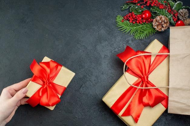 Powyżej widok świątecznego nastroju z ręką trzymającą jeden z pięknych prezentów i szyszek iglastych gałęzi jodły na ciemnym tle