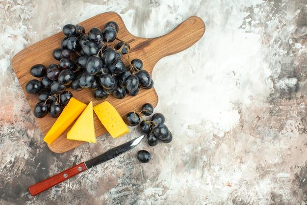 Powyżej widok świeżego pysznego czarnego grona winogron i różnych rodzajów sera na drewnianej desce do krojenia i noża na mieszanym kolorze tła