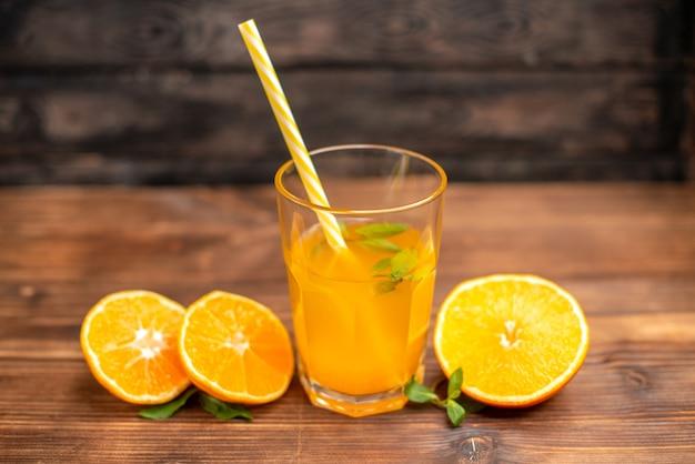 Powyżej widok świeżego soku pomarańczowego w szklance podanego z tubką miętową i pomarańczowymi limonkami na drewnianym stole