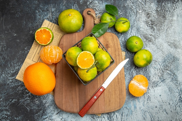 Powyżej widok świeżych owoców cytrusowych z liśćmi na drewnianej desce do krojenia pokrojonej na pół i nożem na szarym stole z gazety