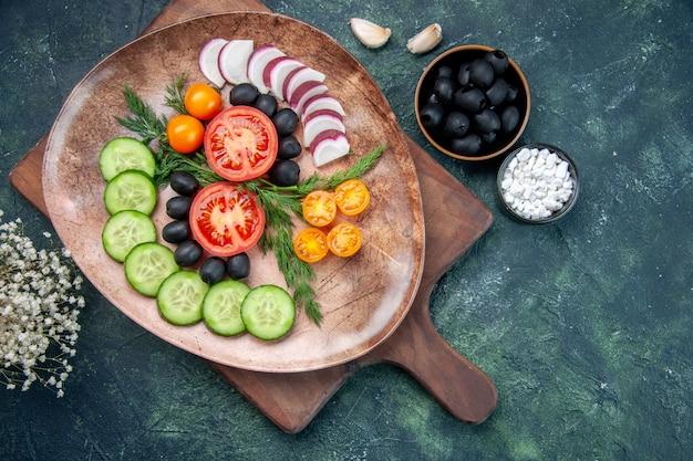 Powyżej widok świeżych pokrojonych warzyw w brązowym talerzu na drewnianej desce do krojenia oliwki w misce sól czosnek kwiat na stole w różnych kolorach
