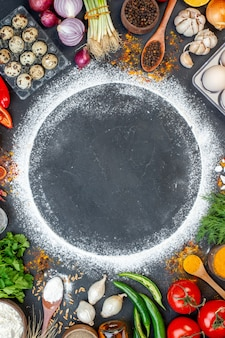 Powyżej widok świeżych różnych zestawów żywności i wolnej przestrzeni z mąką wokół na ciemnym tle color