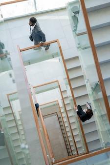 Powyżej widok współczesnych ludzi biznesu poruszających się po schodach w centrum biurowym podczas przychodzenia do pracy