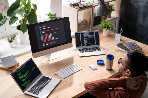 Powyżej widok zaintrygowanego programisty ze bliskiego wschodu w okularach siedzącego przed komputerami i analizującego skrypt internetowy