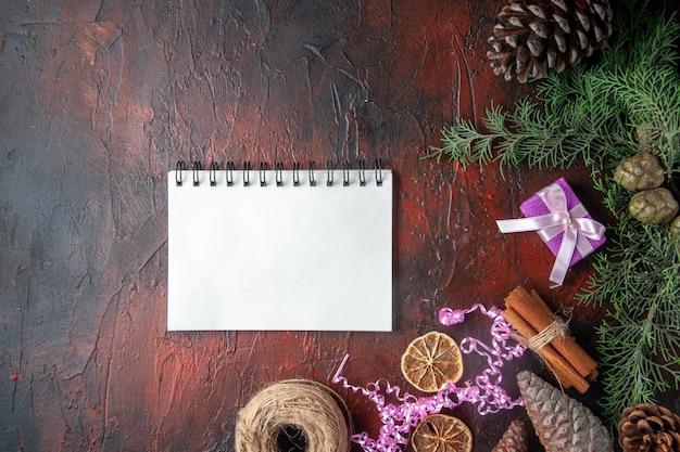 Powyżej widok zamkniętego notatnika z długopisowymi limonkami cynamonowymi i kulką prezentowych szyszek iglastych po lewej stronie na ciemnym tle