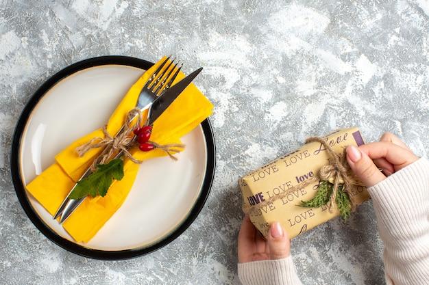Powyżej widok zestawu sztućców do posiłku na białym talerzu i dłoni trzymającej piękny zapakowany prezent na powierzchni lodu
