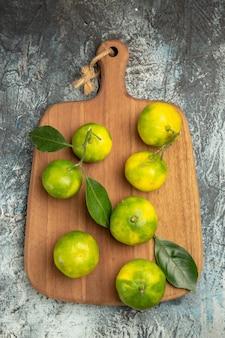 Powyżej widok zielonych mandarynek z liśćmi na drewnianej desce do krojenia na szarym tle