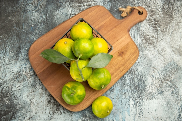 Powyżej widok zielonych mandarynek z liśćmi wewnątrz i na zewnątrz kosza na drewnianej desce do krojenia na szarym stole