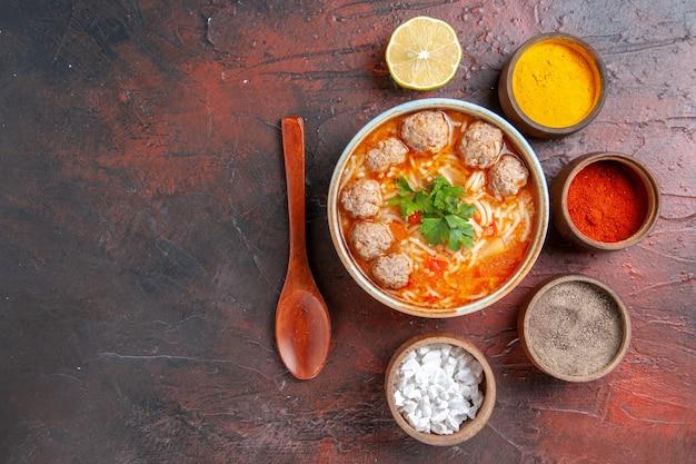 Powyżej widok zupy z klopsikami z makaronem w brązowej misce, łyżką cytrynową i różnymi przyprawami na ciemnym stole