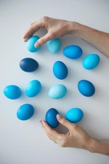 Powyżej widoku tła ręka żeńska układająca kompozycję pomalowanych na niebiesko pisanek na białym, kopia przestrzeń