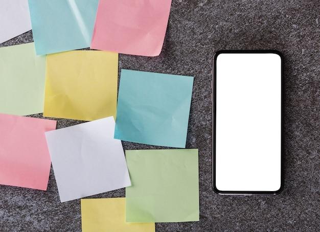 Powyżej wielu pustych list karteczek z pustym ekranem nowoczesnego czarnego inteligentnego telefonu komórkowego
