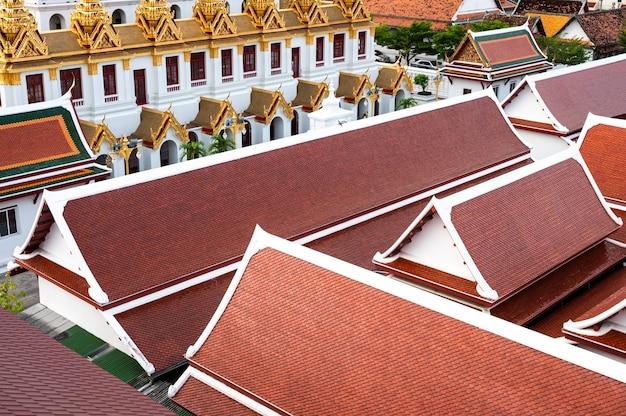 Powyżej zatłoczonego tradycyjnego dachu tajskiej świątyni o konstrukcji szczytowej