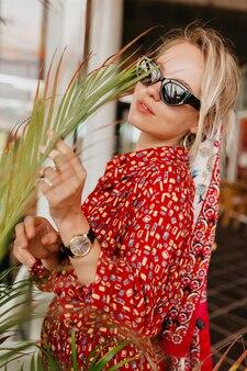 Poza portret atrakcyjnej ładnej kobiety o blond włosach w czarnych okularach i jasnej sukience